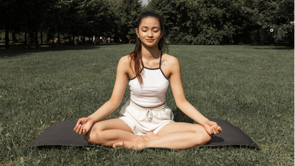 girl meditating in the grass