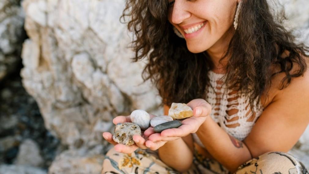 girl holding stones on beach
